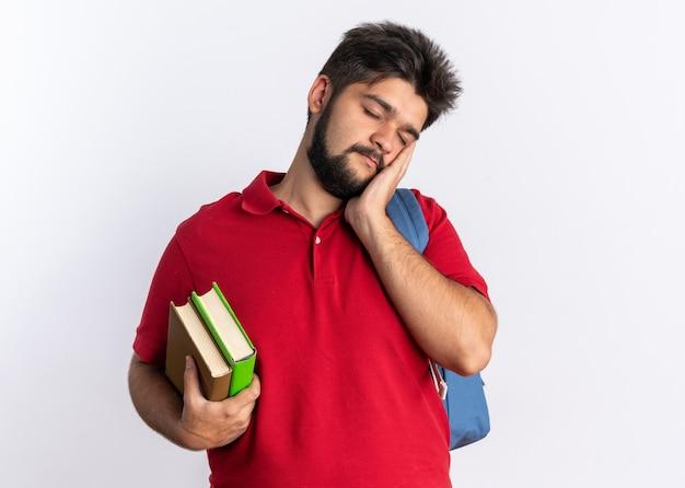 배낭에 노트북을 들고 빨간색 폴로 셔츠에 젊은 수염 난 학생 남자는 흰 벽 위에 서있는 손바닥에 피곤하고 지루한 기대어 머리를 찾고