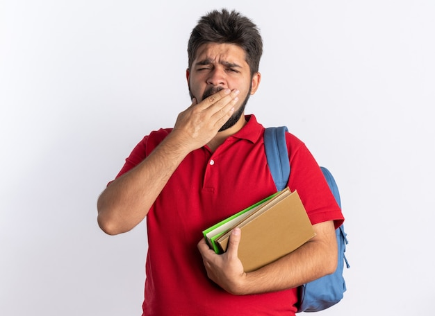白い背景の上に立って疲れて退屈なあくびをしているように見えるノートブックを保持しているバックパックと赤いポロシャツの若いひげを生やした学生の男