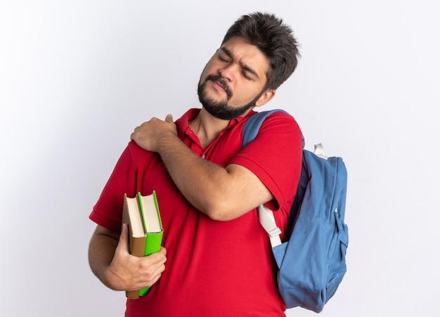 Молодой бородатый студент-парень в красной рубашке поло с рюкзаком, держащим ноутбуки, выглядит нездоровым, трогает его плечо, чувствуя боль стоя