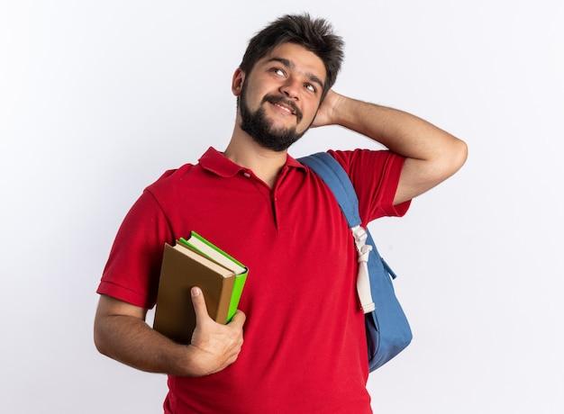 赤いポロシャツを着た若いひげを生やした学生の男が、白い壁の上に立って、笑顔の思考のポジティブな立っているノートを持ってバックパック
