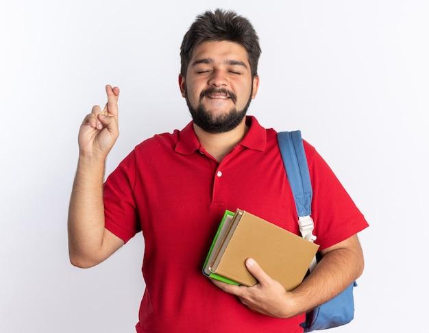 Молодой бородатый студент-парень в красной рубашке поло с рюкзаком держит тетради, загадывая желание, скрещивая пальцы с выражением надежды стоя