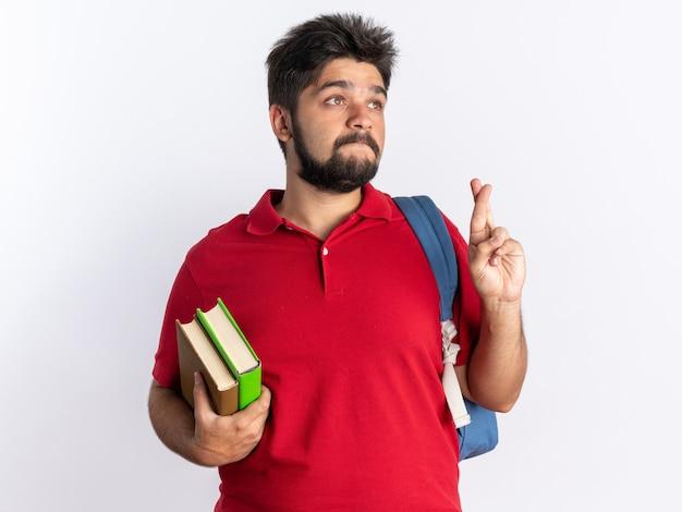 赤いポロシャツを着た若いひげを生やした学生の男が、ノートを持ってバックパックを持ち、希望の表情を交差させて指を立てて願い事をする