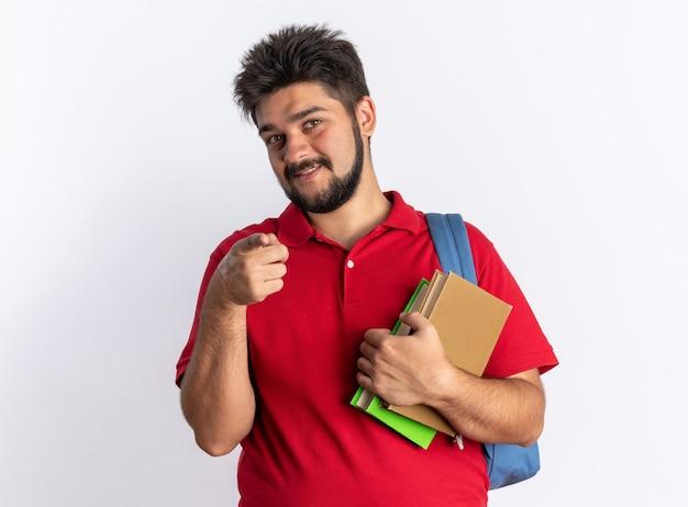 白い壁の上に立っている幸せで肯定的な笑顔の人差し指で指しているノートを保持しているバックパックを持つ赤いポロシャツの若いひげを生やした学生の男