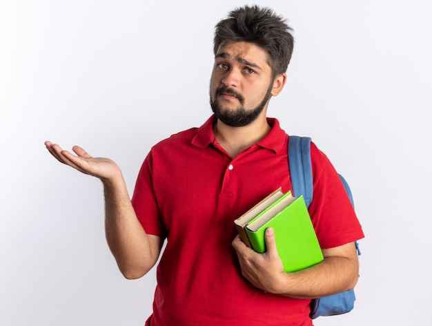 赤いポロシャツを着た若いひげを生やした学生の男が、ノートを持ったバックパックを持ち、悲しい表情で立って手の腕でコピースペースを提示