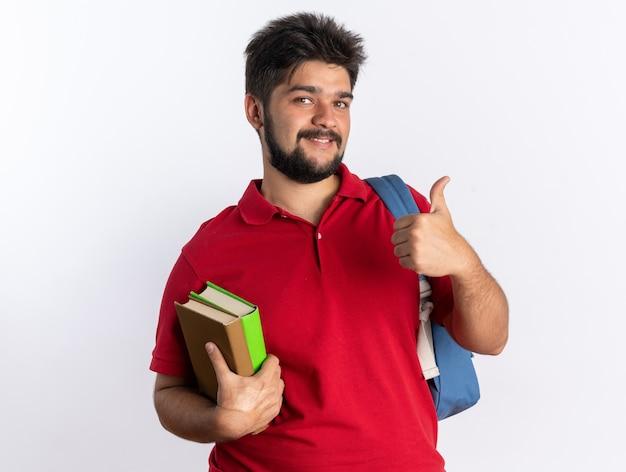 白い壁の上に立って陽気な笑顔を見せるノートを持ったバックパックと赤いポロシャツを着た若いひげを生やした学生男