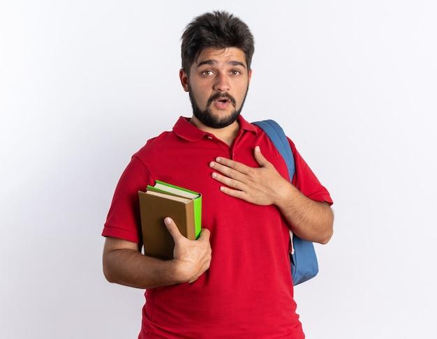 ノートを持ったバックパックを持つ赤いポロシャツを着た若いひげを生やした学生の男は、白い壁の上に立っている彼の胸に手を握って驚いた