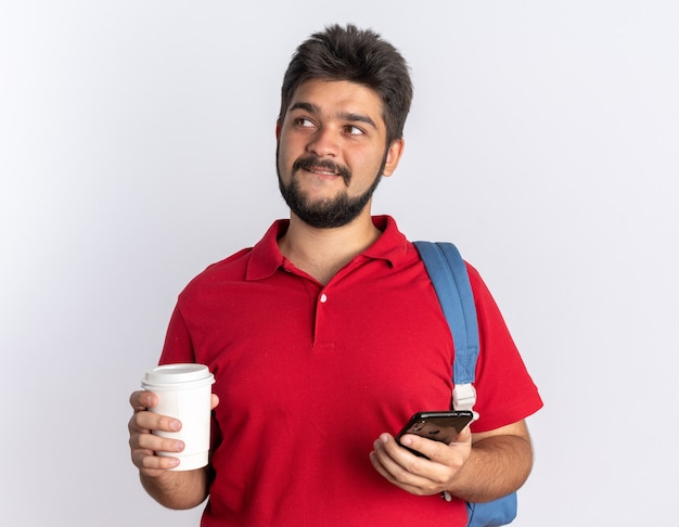 スマートフォンとコーヒー カップを保持しているバックパックを持つ赤いポロシャツの若いひげを生やした学生の男が白い壁の上に立っている顔にずるい笑顔でよそ見