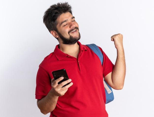 赤いポロシャツを着た若いひげを生やした学生の男が、白い壁の上に立ってスマートフォンを握りこぶしを握り締めて幸せで興奮しているバックパックを持っている