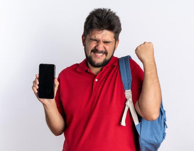 スマートフォンを保持しているバックパックで赤いポロシャツを着た若いひげを生やした学生の男が幸せで興奮して拳を握りしめている