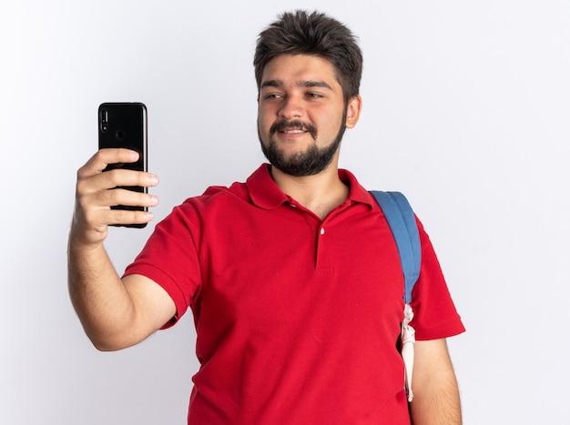 흰 벽 위에 유쾌하게 서서 웃고있는 스마트 폰을 들고 배낭과 빨간색 폴로 셔츠에 젊은 수염 난 학생 남자
