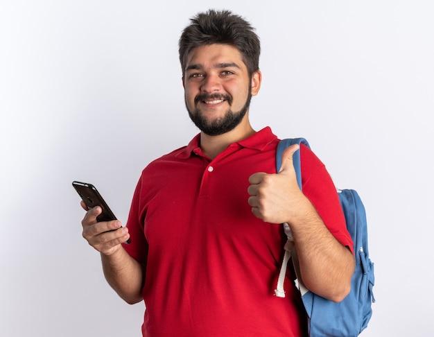 スマートフォンを保持しているバックパックを持つ赤いポロシャツの若いひげを生やした学生男