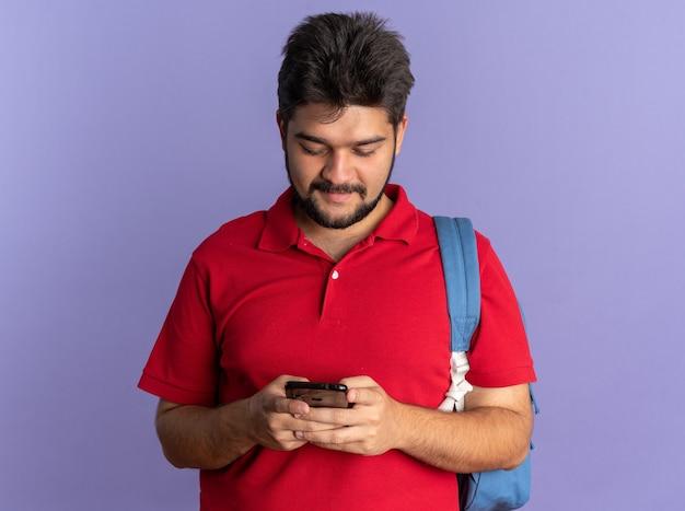 自信を持って立っているように見えるテキスト メッセージを書くスマートフォンを保持しているバックパックと赤いポロシャツの若いひげを生やした学生の男