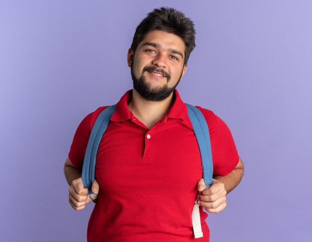 赤いポロシャツを着た若いひげを生やした学生の男がバックパックを見て、自信を持って幸せでポジティブな立ち姿を笑顔で見ている