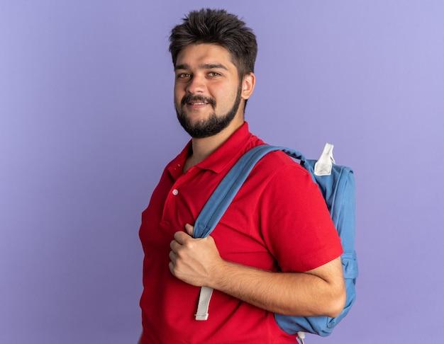 自信を持って立っている笑顔のバックパックと赤いポロシャツの若いひげを生やした学生男