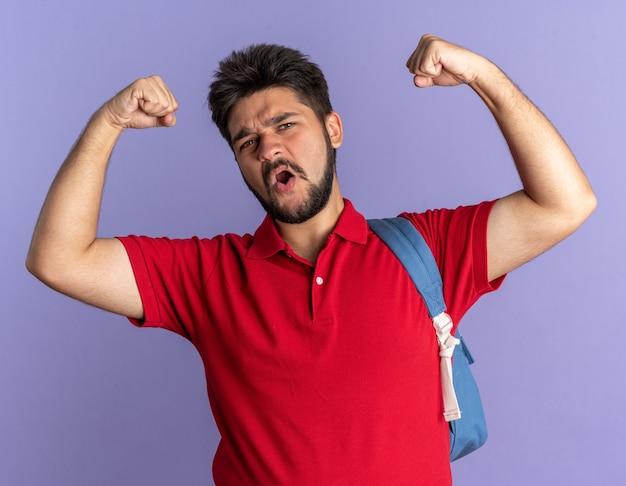赤いポロシャツを着た若いひげを生やした学生の男が、幸せで自信に満ちた勝者のようにポーズをとった拳を上げるバックパックを持つ