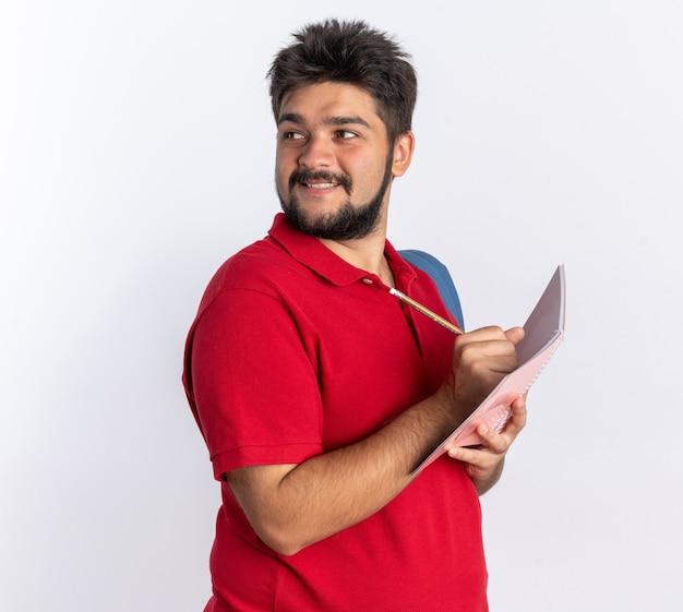白い壁の上に立って自信を持って笑顔を見てノートに書くバックパックと赤いポロシャツの若いひげを生やした学生男