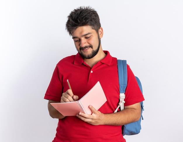立っている自信に満ちた笑顔を見てノートに書くバックパックと赤いポロシャツの若いひげを生やした学生男