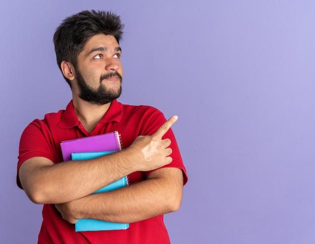 Giovane studente barbuto in polo rossa con libri che guardano da parte con un sorriso sul viso che punta con il dito indice sul lato in piedi sul muro blu