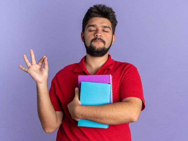 Giovane studente barbuto in polo rossa con in mano libri che fa un gesto di meditazione rilassante con gli occhi chiusi in piedi sul muro blu