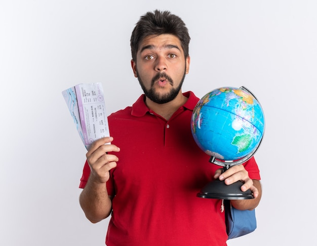 Young bearded student guy in red polo shirt with backpack holding airline tickets and globe looking surprised standing