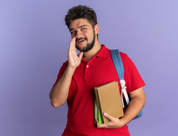 Ragazzo giovane studente barbuto in maglietta polo rossa con zaino in possesso di libri che guarda l'obbiettivo sussurrando un segreto con la mano vicino alla bocca in piedi felice e positivo su sfondo blu