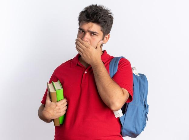 Giovane studente barbuto in polo rossa con zaino in possesso di quaderni scioccato che copre la bocca con la mano in piedi sul muro bianco
