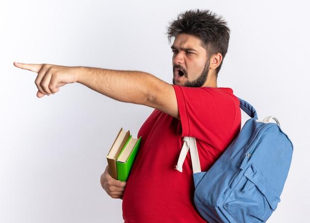 Giovane studente barbuto in polo rossa con zaino che tiene quaderni guardando da parte con faccia arrabbiata che grida indicando con il dito indice qualcosa in piedi sul muro bianco