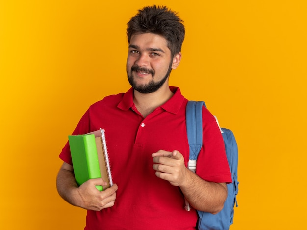Ragazzo giovane studente barbuto in maglietta polo rossa con zaino tenendo i notebook puntando con il dito indice alla telecamera sorridendo allegramente in piedi su sfondo arancione