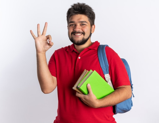 Giovane studente barbuto in polo rossa con zaino in possesso di quaderni che sorride allegramente mostrando segno ok in piedi sul muro bianco
