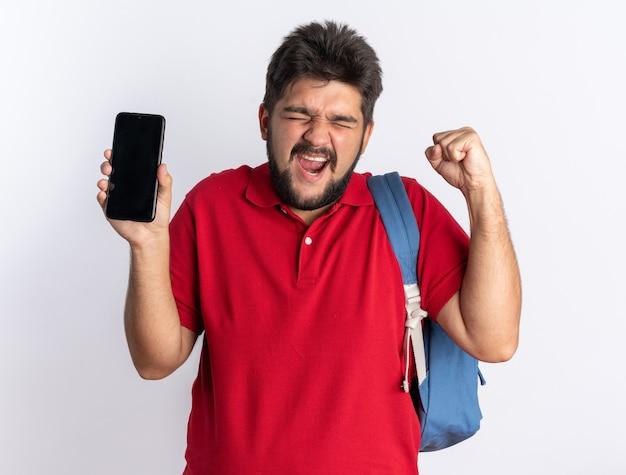 Giovane studente barbuto in polo rossa con zaino che tiene in mano lo smartphone che stringe il pugno felice ed eccitato in piedi