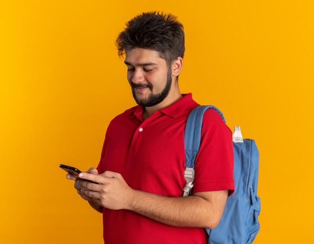 Giovane studente barbuto in polo rossa con zaino che tiene in mano lo smartphone e lo guarda sorridendo allegramente felice e positivo in piedi sul muro arancione