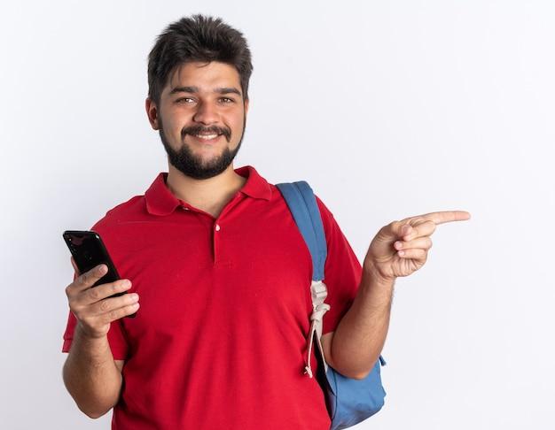 Giovane studente barbuto in polo rossa con zaino che tiene smartphone puntato con il dito indice sul lato sorridente fiducioso in piedi sul muro bianco