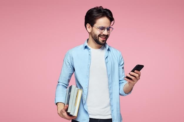笑顔で携帯電話を使用して本を持っている若いひげを生やした学生