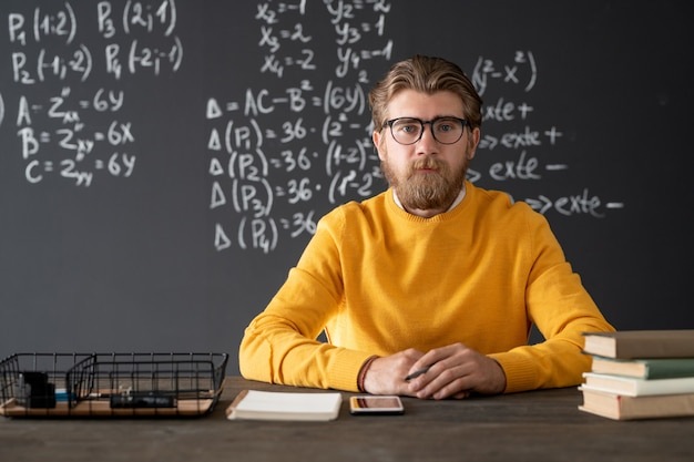 Young bearded teacher of algebra sitting by table on blackboard with formulas and equations during online lesson in classroom