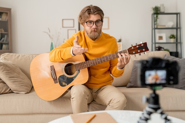 Young bearded teacher of music explaining something or answering question of online audience during lesson in home environment