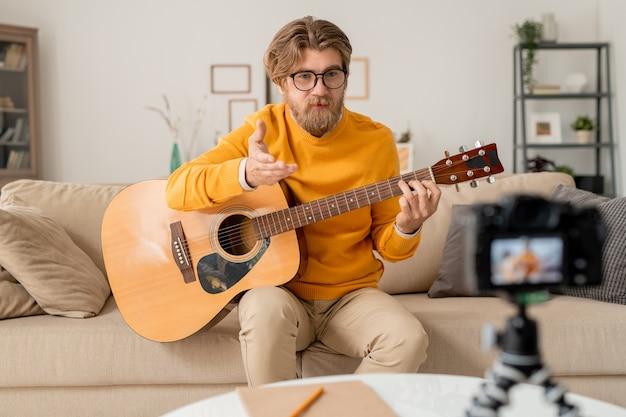 Молодой бородатый учитель музыки что-то объясняет или отвечает на вопросы онлайн-аудитории во время урока в домашней обстановке