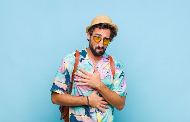 Молодой бородатый турист, чувствующий себя встревоженным, больным, больным и несчастным, страдает от болезненной боли в животе или гриппа