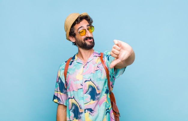 Young bearded tourist man feeling cross, angry, annoyed, disappointed or displeased, showing thumbs down with a serious look