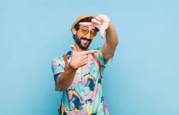幸せで、フレンドリーで、前向きで、笑顔で、手で肖像画やフォトフレームを作る若いひげを生やした観光客の男性
