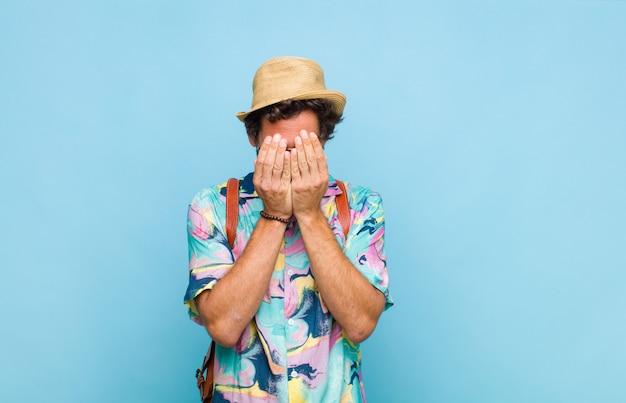 Молодой бородатый турист мужчина грустит, расстроен, нервничает и подавлен, закрывает лицо обеими руками, плачет