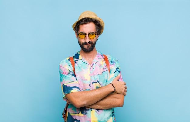 Молодой бородатый турист, грустный, расстроенный или сердитый, смотрит в сторону с отрицательным отношением, хмурясь в знак несогласия