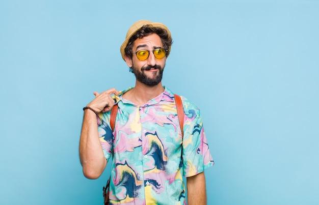 Молодой бородатый турист, чувствуя стресс, тревогу, усталость и разочарование, дергает за шею рубашки и выглядит разочарованным из-за проблемы