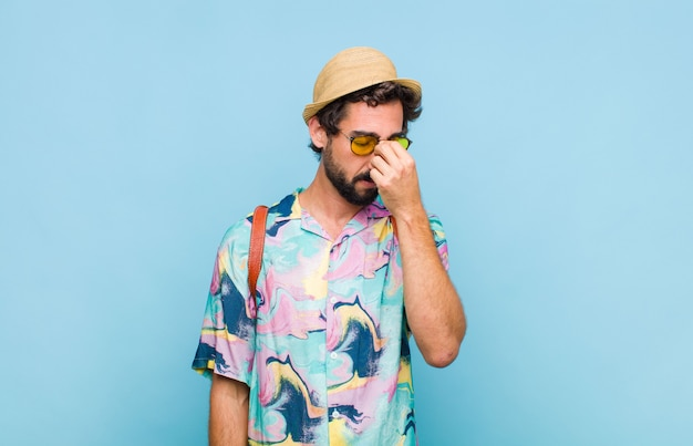 Молодой бородатый турист, чувствующий себя напряженным, несчастным и разочарованным, трогает лоб и страдает от сильной мигрени