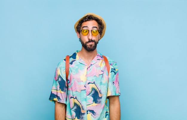 Молодой бородатый турист, выглядящий глупо и смешно, с глупым косоглазым выражением лица, шутит и дурачит
