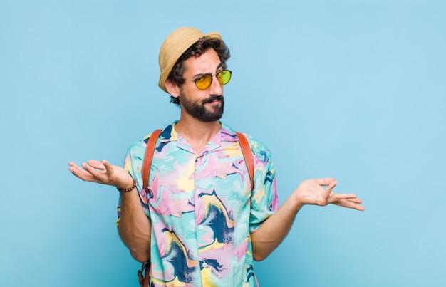 Молодой бородатый турист, выглядящий озадаченным, сбитым с толку и подчеркнутым, раздумывает о разных вариантах, чувствует себя неуверенно