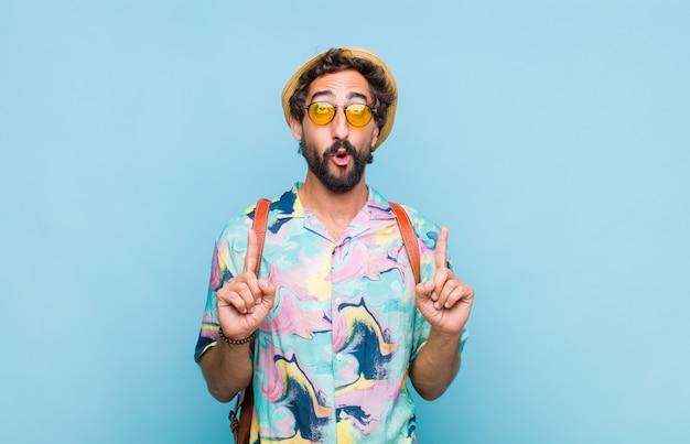Молодой бородатый турист, выглядящий шокированным, удивленным и открытым ртом, показывает вверх обеими руками, чтобы скопировать пространство