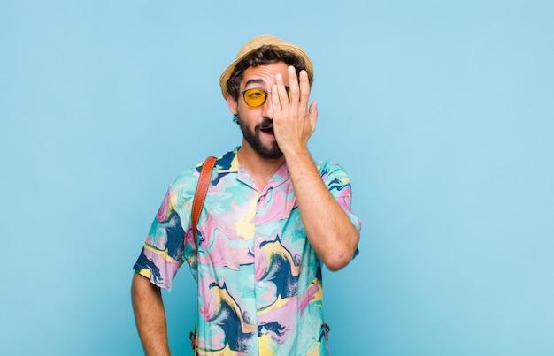 Молодой бородатый турист, выглядящий сонным, скучающим и зевающим, с головной болью и одной рукой, закрывающей половину лица