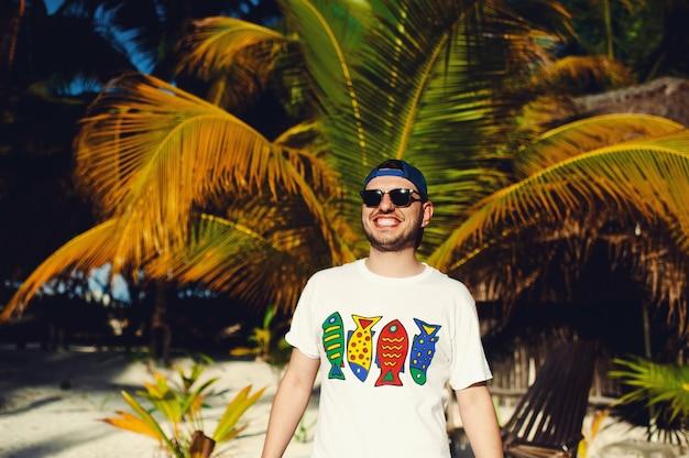Молодой бородатый турист, широко улыбаясь на фоне пальм