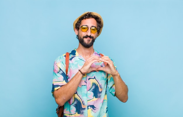 Young bearded tourist man smiling and feeling happy, cute, romantic and in love, making heart shape with both hands