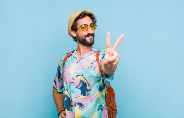 Young bearded tourist man smiling and looking happy, carefree and positive, gesturing victory or peace with one hand
